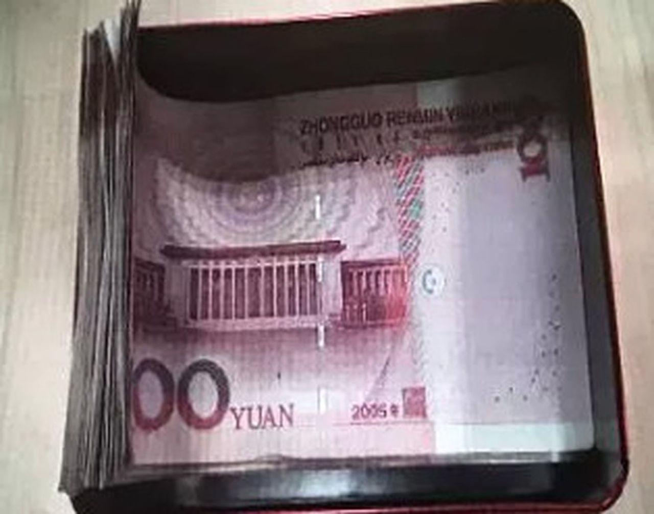 紅色月餅盒內裝了滿滿的現金。(視頻截圖)