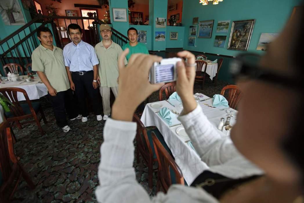 羅珊正在為釋放後找到居住處的維吾爾人拍照,左至右為分別為:Abdulla Abd...