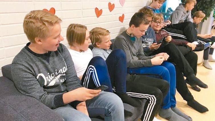 高年級學生聚在一起研究手機上的資訊。 圖/英國廣播公司