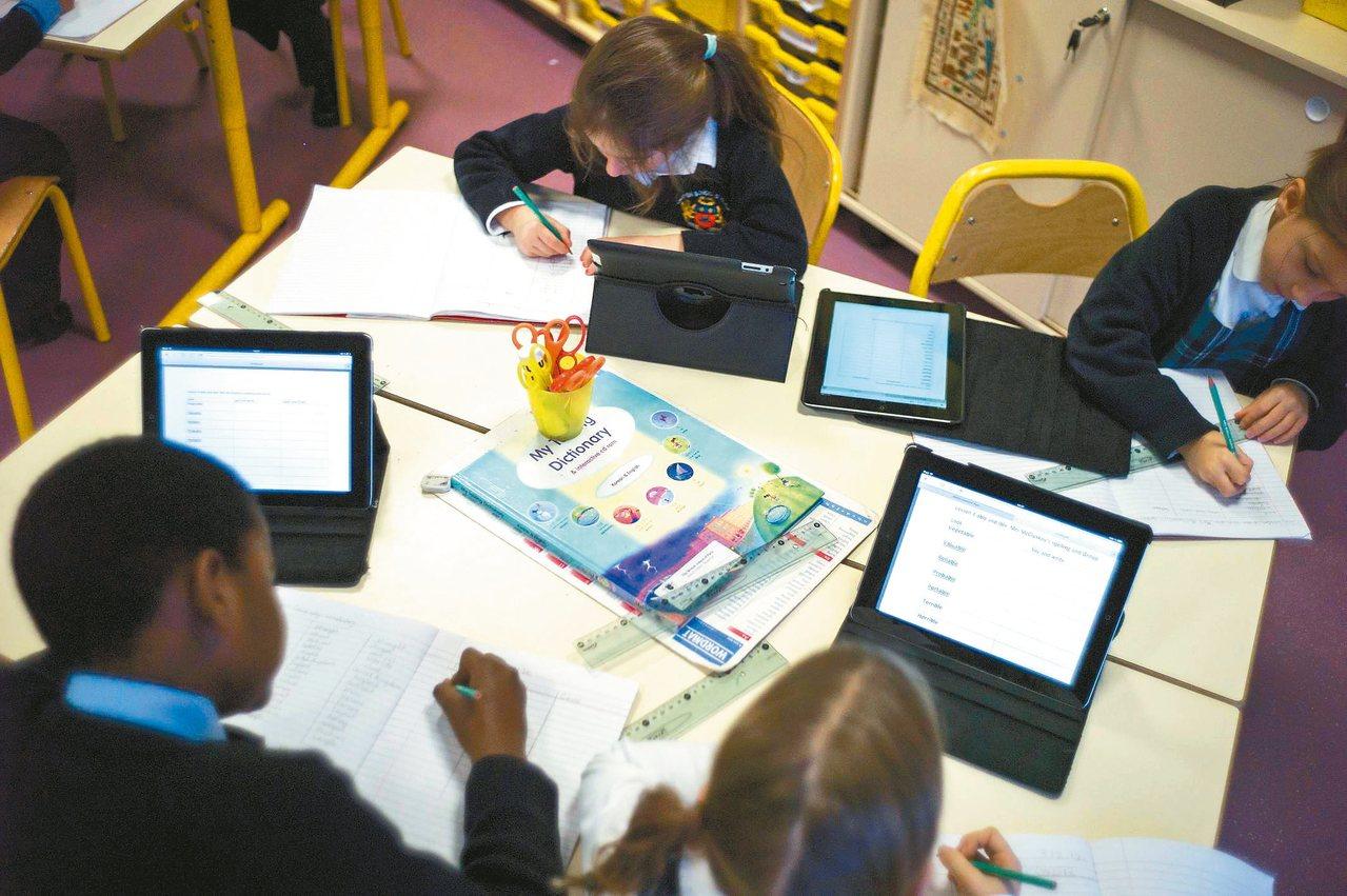 學生在課堂上利用平板電腦輔助學習。 法新社