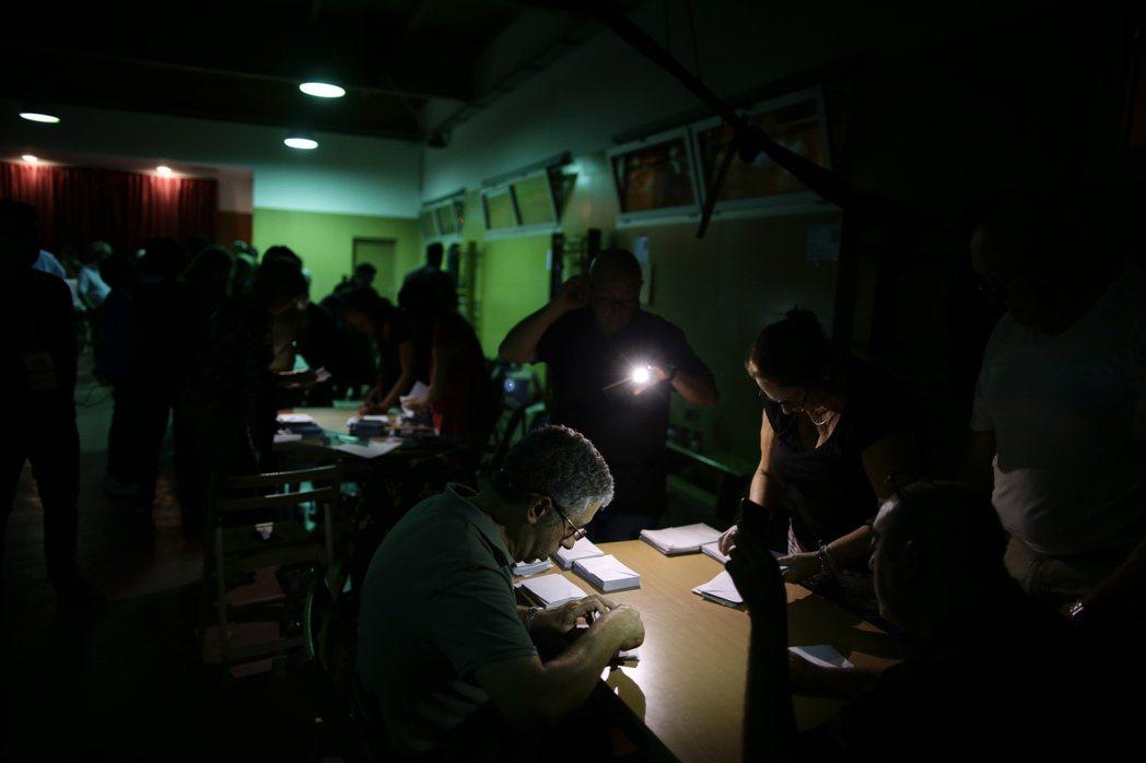 加泰隆尼亞1日公投後,巴塞隆納的一個投票所停電,計票人員利用手機光線開票。 美聯...
