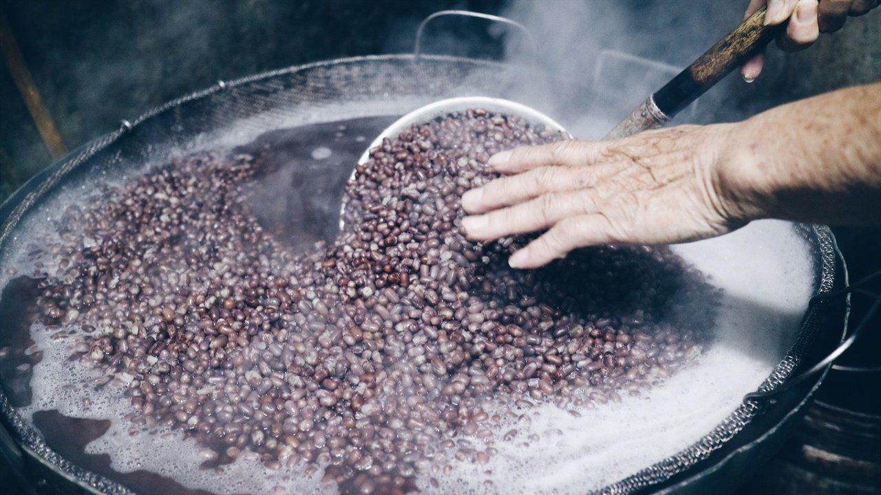 ◭ 所有餡料都是手工製做,前方的鐵板上在煎著餅皮,後面的爐上在熬著紅豆,「選用萬...