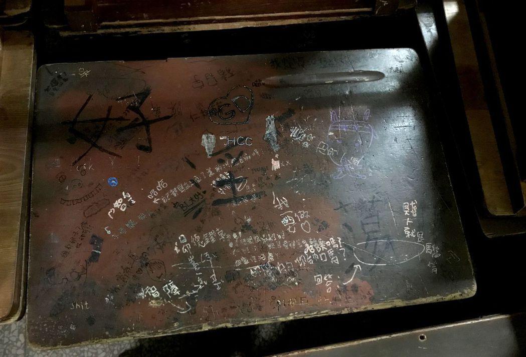 淘汰的課桌椅上,簽字筆、立可白塗滿青春的記憶。 記者洪敬浤/攝影