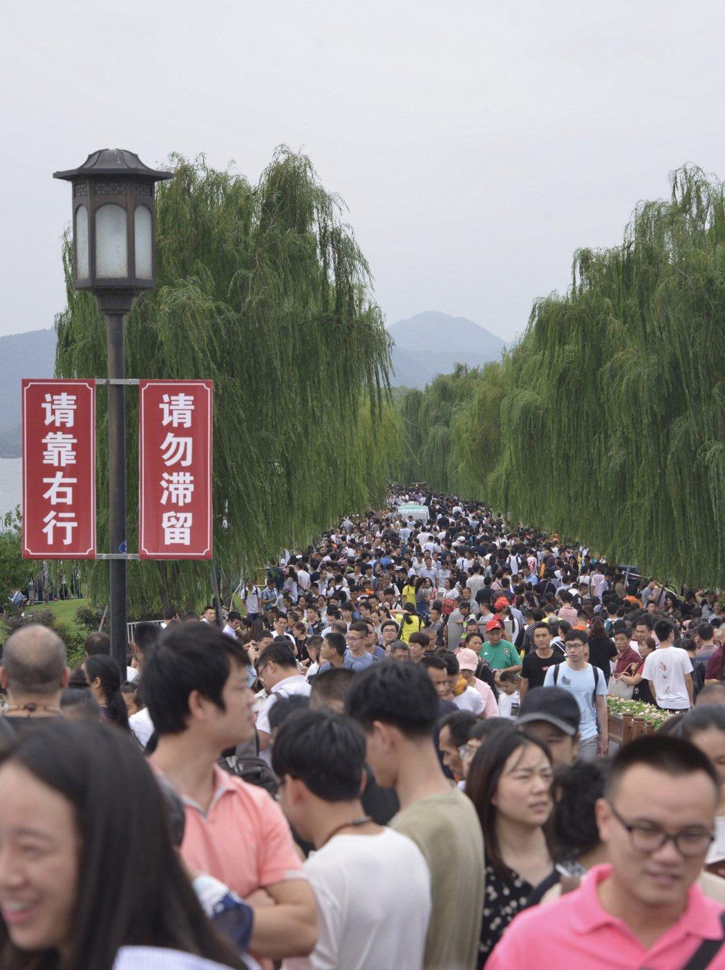 大量遊客湧入西湖斷橋,西湖設置單行線疏導人潮。 中新社