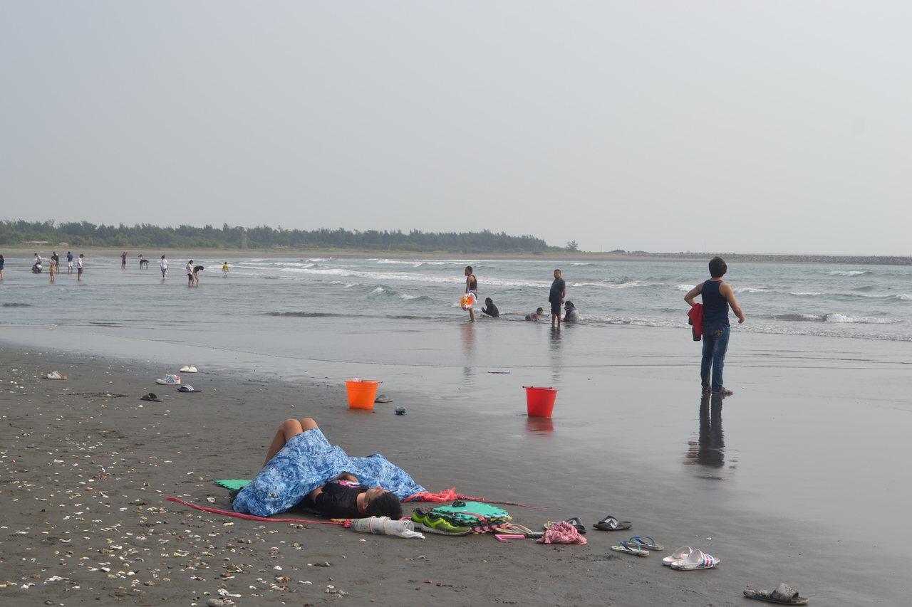 台南市漁光島月牙灣海灘中秋節吸引民眾弄潮、享受日光浴。記者鄭惠仁/攝影