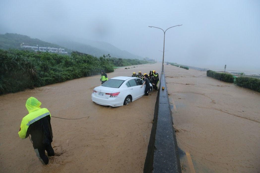 今年6月2日,北海岸暴雨造成台2線嚴重積水,一輛轎涉水熄火在半路,救難人員設法把...