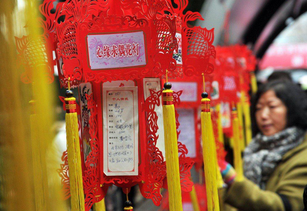 上海人民公園在情人節懸挂起百餘盞「心緣求偶花燈」,長廊上貼著尋覓姻緣者的基本信息...