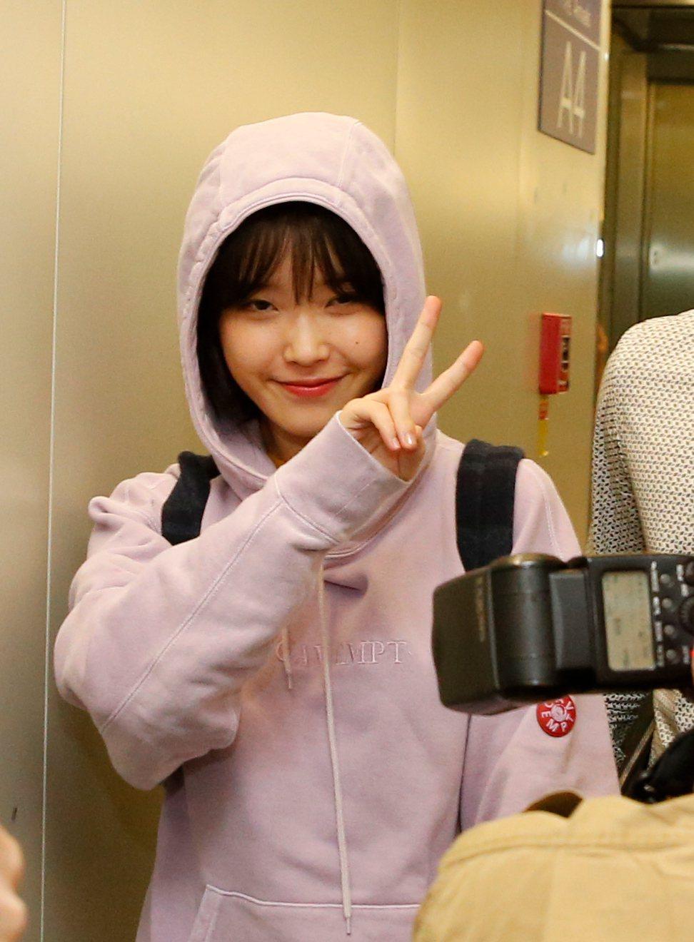 韓星IU搭乘KE-691班機抵達桃園機場,她穿著粉紅色帽T、牛仔褲與運動鞋現身,...