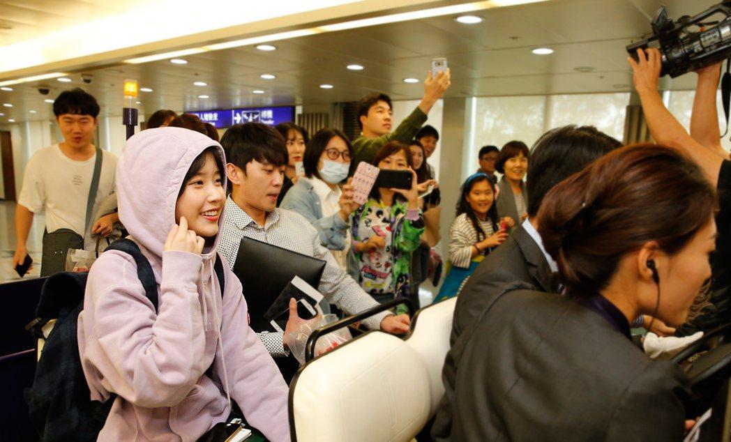 韓星IU搭乘KE-691班機抵達桃園機場,在管制區內的粉絲把握機會拍照。記者鄭超...