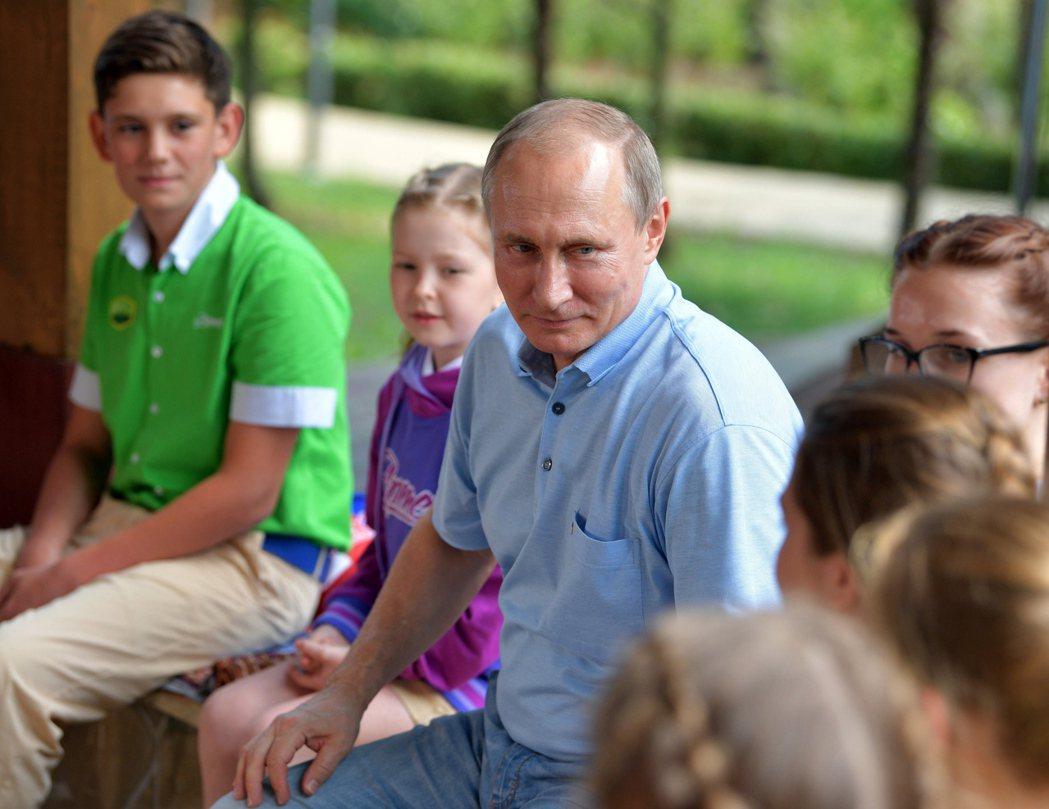 俄國面臨低出生率的問題,圖為總統普亭造訪克里米亞一處兒童遊樂場。 美聯社