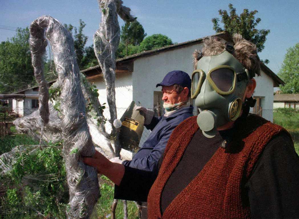 1999年5月北約對塞爾維亞投擲石墨炸彈後,當地居民戴著防毒面具清除炸彈釋放的導...