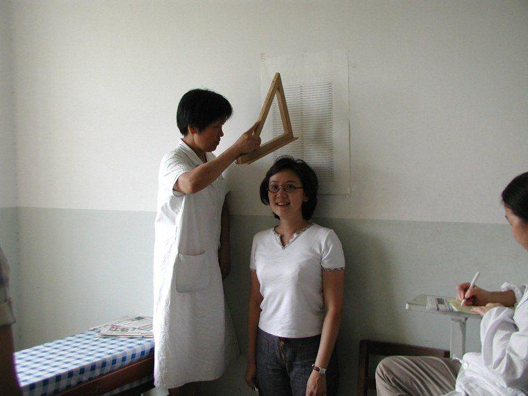 2002年9月上海復旦大學新生體檢,醫護人員用三角板充當量身高器具。 本報資料照