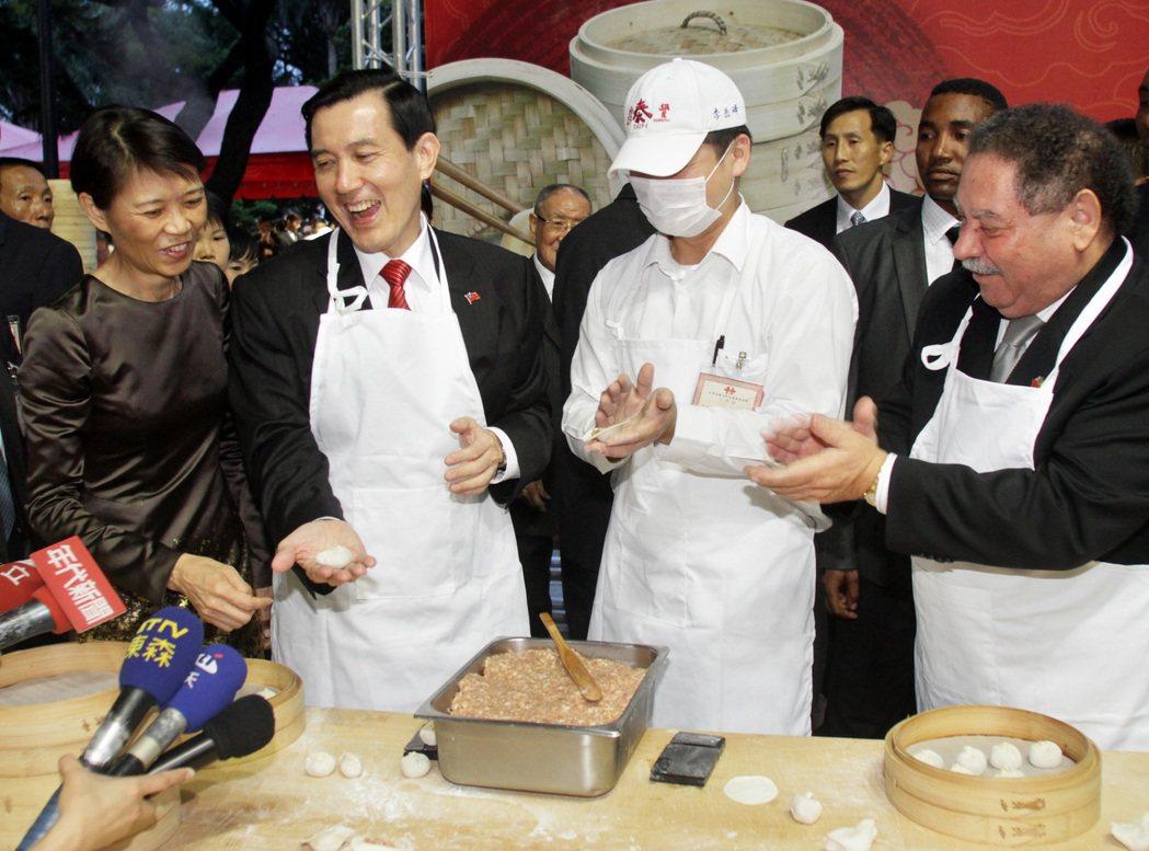 2010年,馬英九總統(左二)和聖多美普林西比總統梅尼士(右)一起穿上圍裙包小籠...