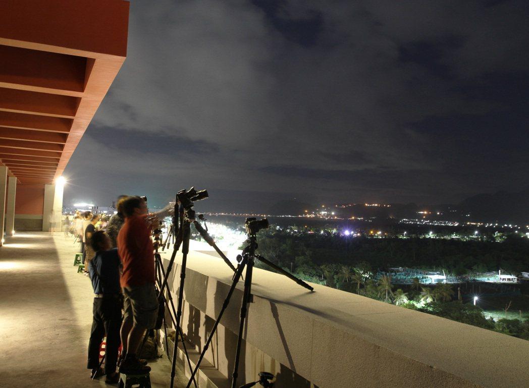 國慶煙火今晚在台東卑南溪出海口施放,附近至高點都有許多民眾架腳架準備拍攝煙花。記...