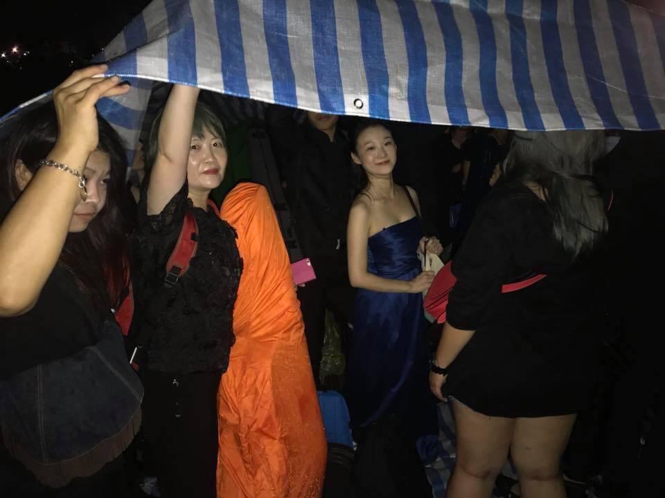 樂團成員只能躲在人肉帳篷躲雨。圖╱馮楚軒提供