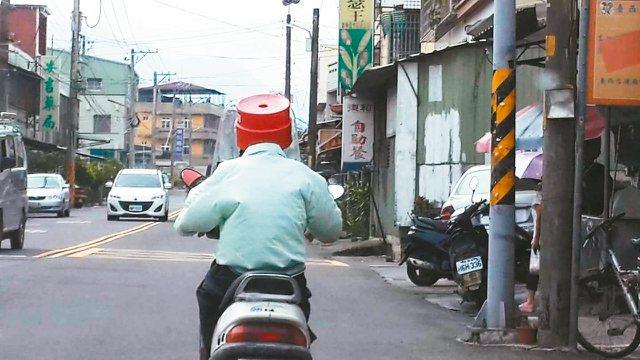 古坑鄉有老人怕警察取締未戴安全帽,異想天開用紅色小圓椅當安全帽。