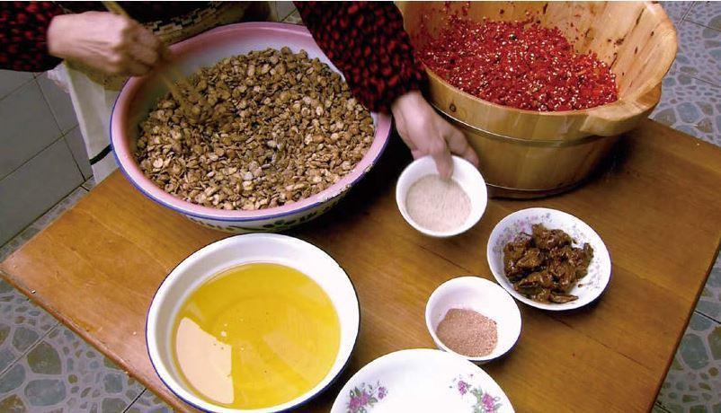 陳婆婆把黴好的蠶豆瓣倒入剁碎的新鮮紅辣椒裏,她要抓緊時間調味,趁著好天氣晾曬發酵...