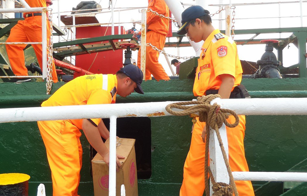海巡人員從日安升油輪的密艙口搬出私菸。記者林保光/攝影