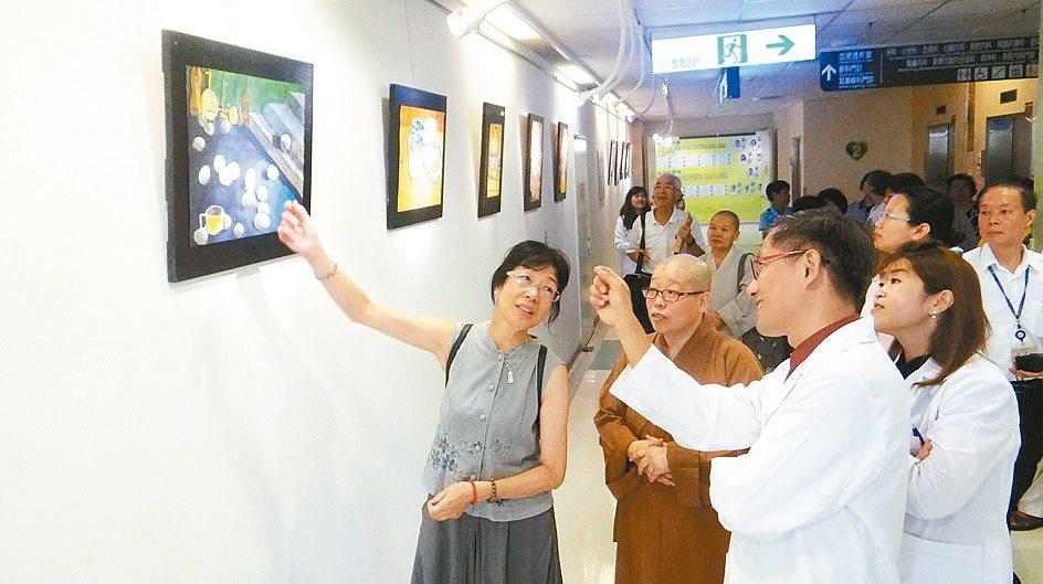 曾媽媽(左)說明兒子作品與創作歷程,讓醫護人員十分感動。 記者蔡維斌/攝影