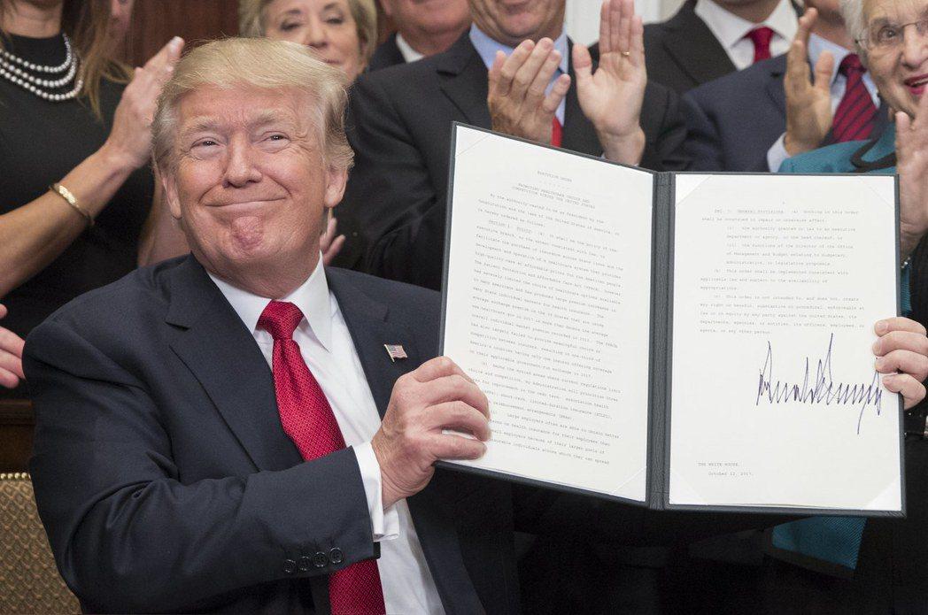 川普簽署行政命令後,高興得舉起來展示。歐新社
