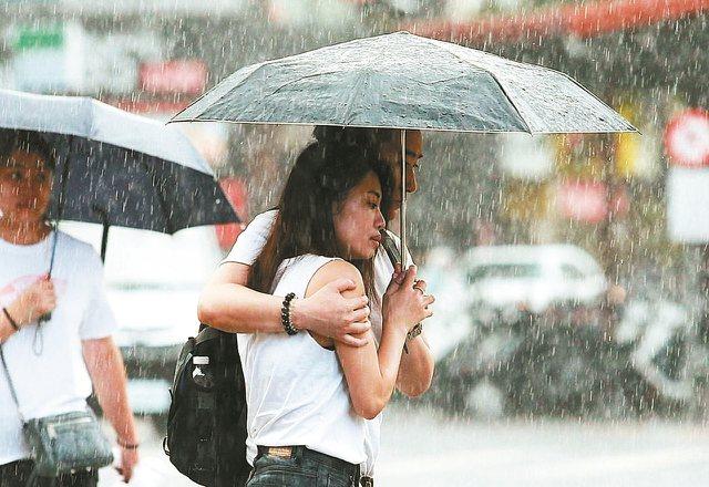 昨天東北部有局部大雨或豪雨,情侶瑟縮在傘下,緩步前進。