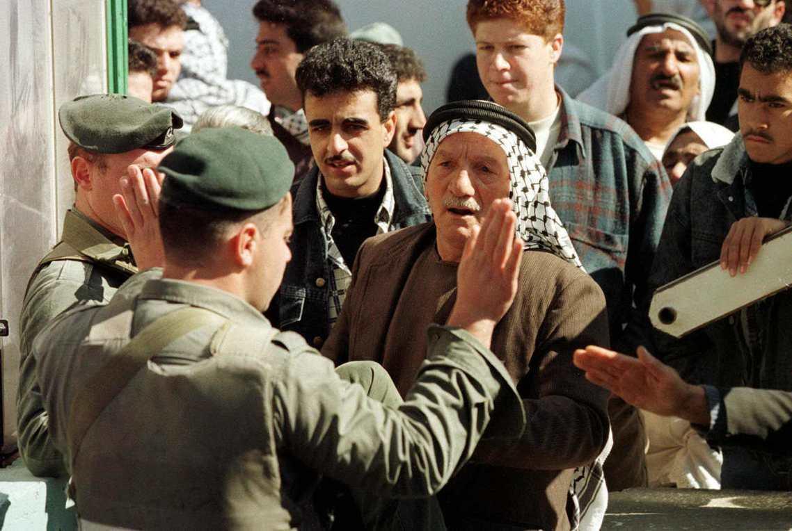 易卜拉欣清真寺寺外,巴勒斯坦悼念者與以色列軍人的推擠。 圖/路透社