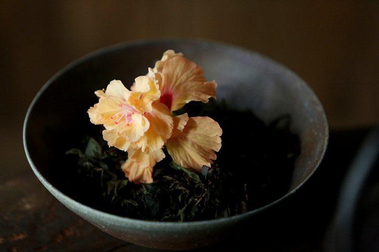已泡開的茶葉上擺放鮮花,生與死、陰鬱與柔美的對比,形成強烈美感。圖/謝小曼提供