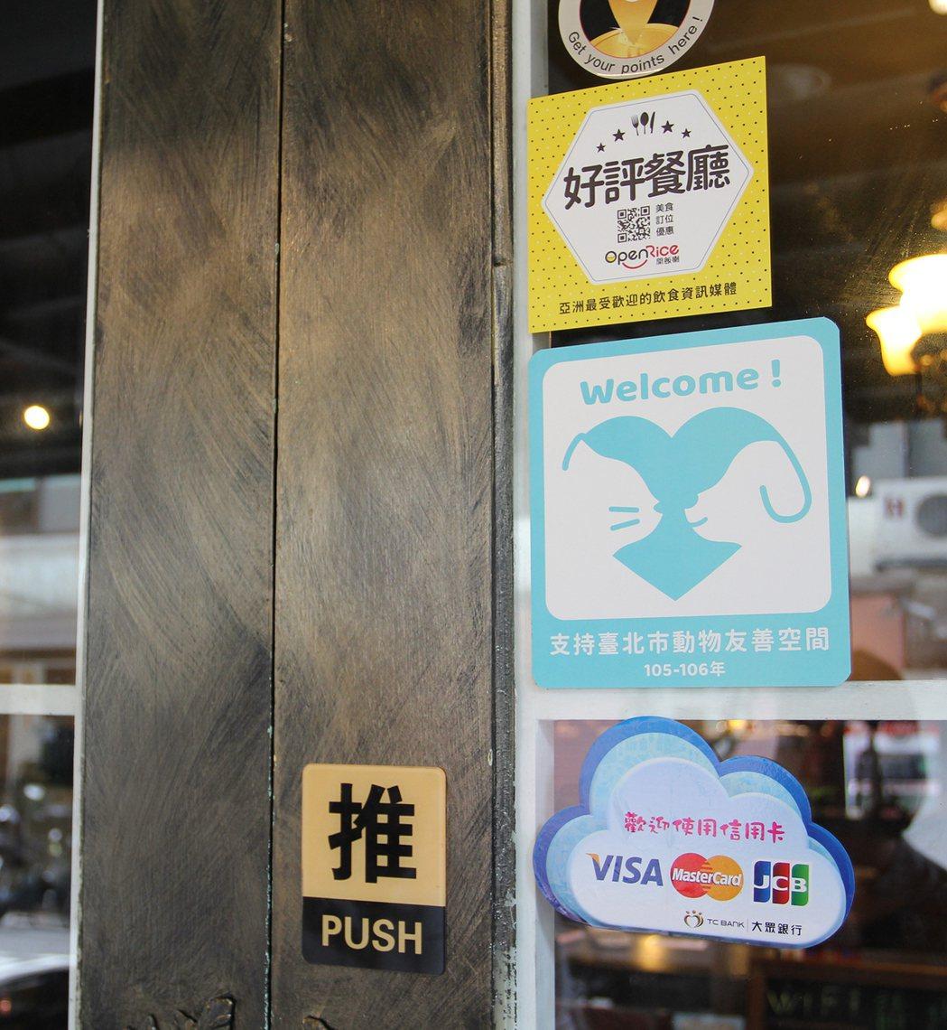 動物友善服務優良店家-騎士維克大門上貼著支持臺北市動物友善空間的藍色貼紙。圖/有...