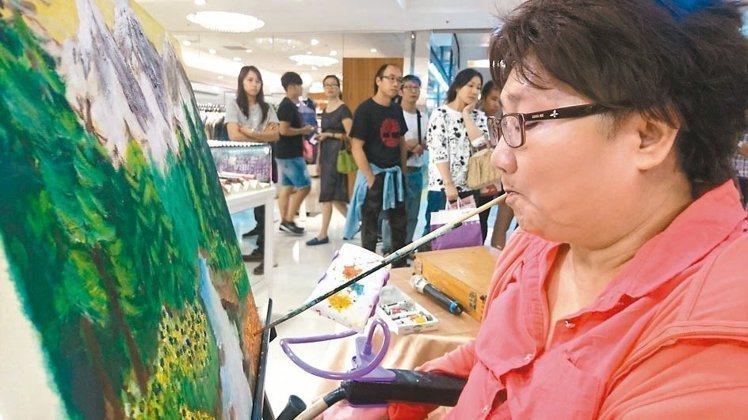 口足畫家謝美容以口繪油畫,畫出她的生命力和人生態度。 圖/李佳鎂提供