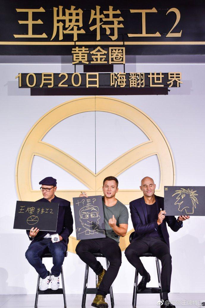 「金牌特務2:機密對決」導演馬修范恩寫下大陸片名「王牌特工」,中為泰隆艾格頓,右