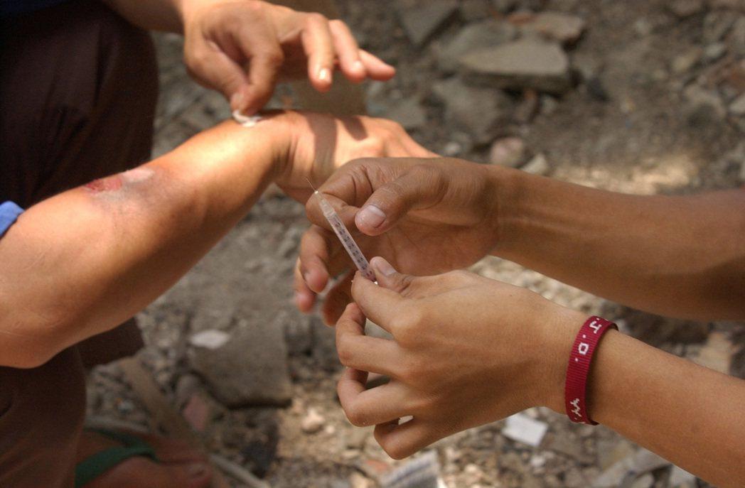 1名提供乾淨針頭的工作人員教導1名海洛因吸毒者如何替針頭消毒。 (美聯社)