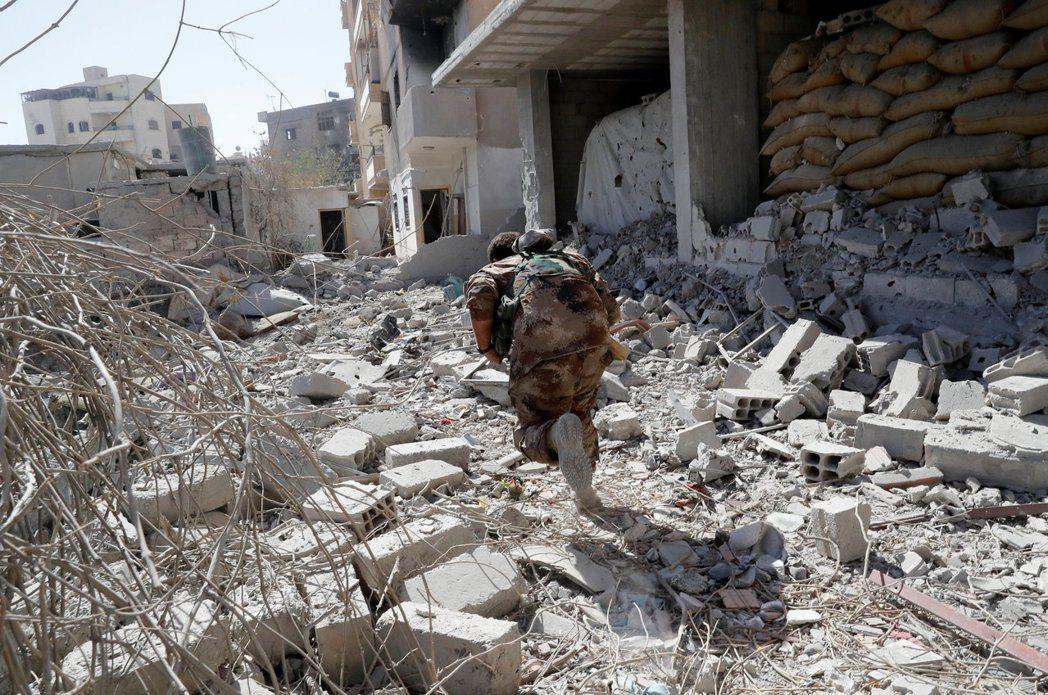 拉卡城內一名聯軍士兵正尋找掩護,避免遭IS狙擊手射殺。 路透
