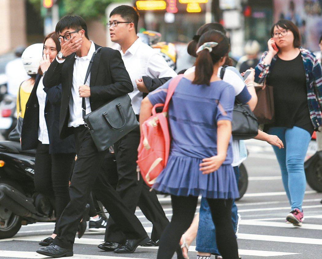 近年台灣薪資水準未見提升,年輕人對薪水的期望值已經下降,圖為街頭的年輕上班族。...