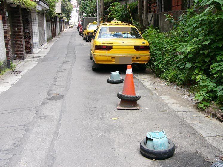 中和市景新街曾遭人放置輪胎、破花盆等雜物霸占停車位。 記者王長鼎/攝影
