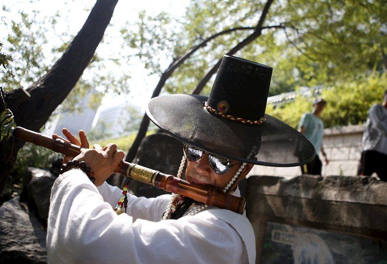 一名穿著韓服的街頭藝人在清溪川邊演奏傳統樂器。 圖/路透社