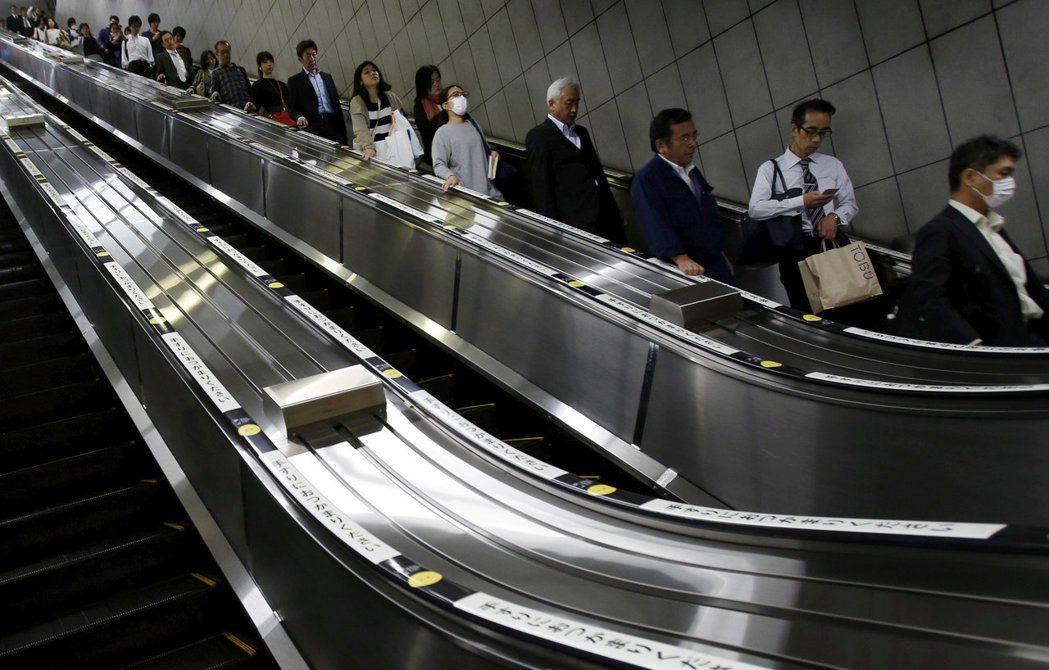 日本經濟低迷多年,許多企業被迫削減成本因應。圖為東京一個地鐵站的電扶梯。 路透