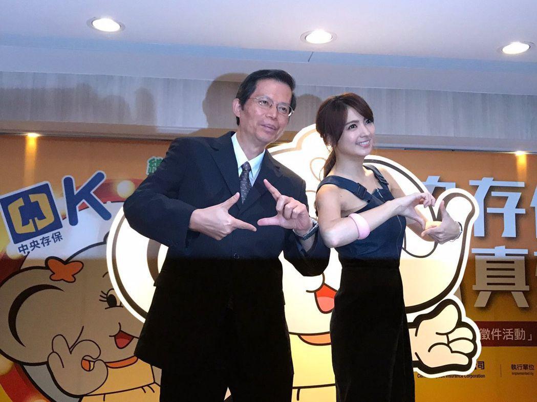 中央存保公司副總經理蘇財源(左)與代言人藝人阿喜,在會中比起創意手勢,期望這次徵...