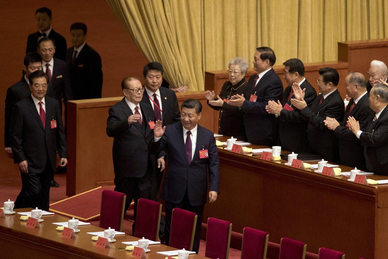 中共19大18日在北京開幕。前後三位中共中央總書記進入會場,受到代表熱烈鼓掌歡迎...