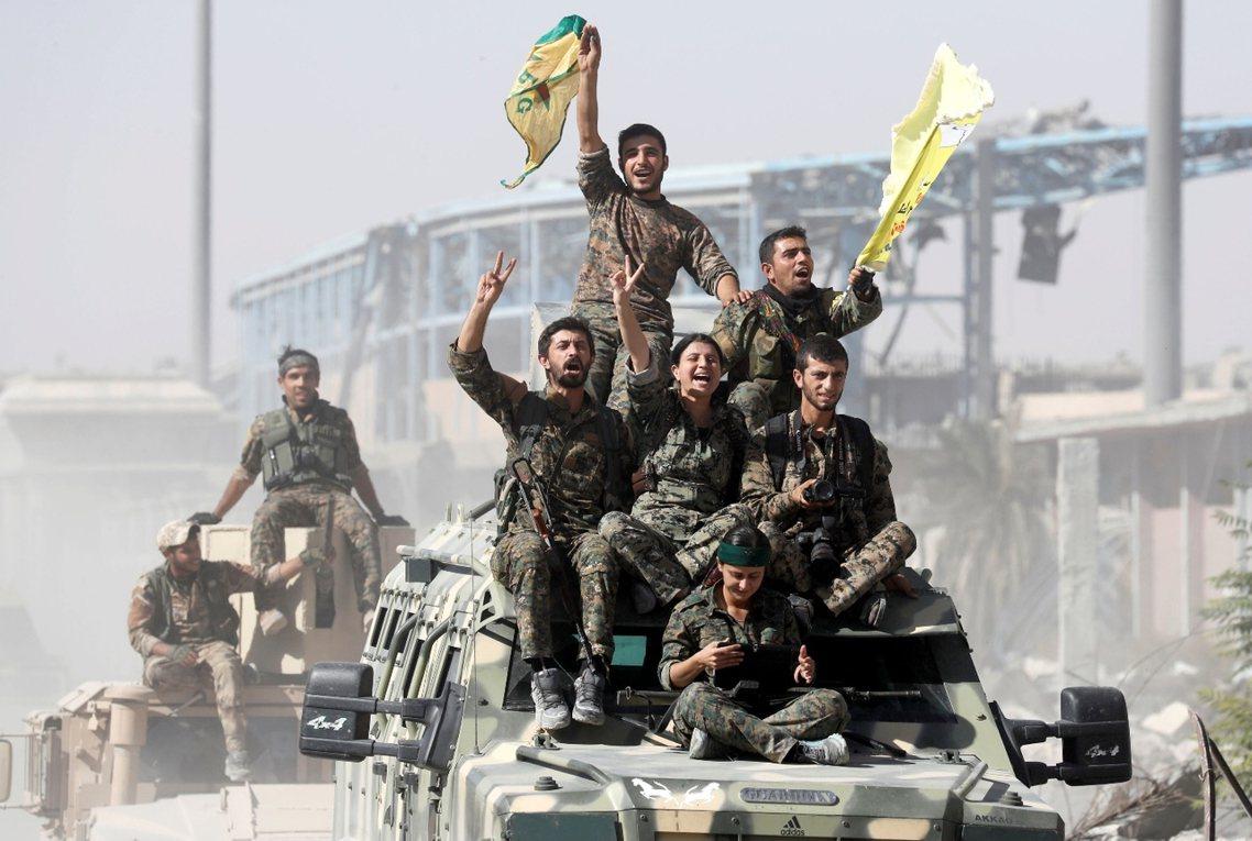 當聳立在拉卡國家醫院的最後一面ISIS黑旗,被庫德戰士扯下後,敘利亞北部城市——...