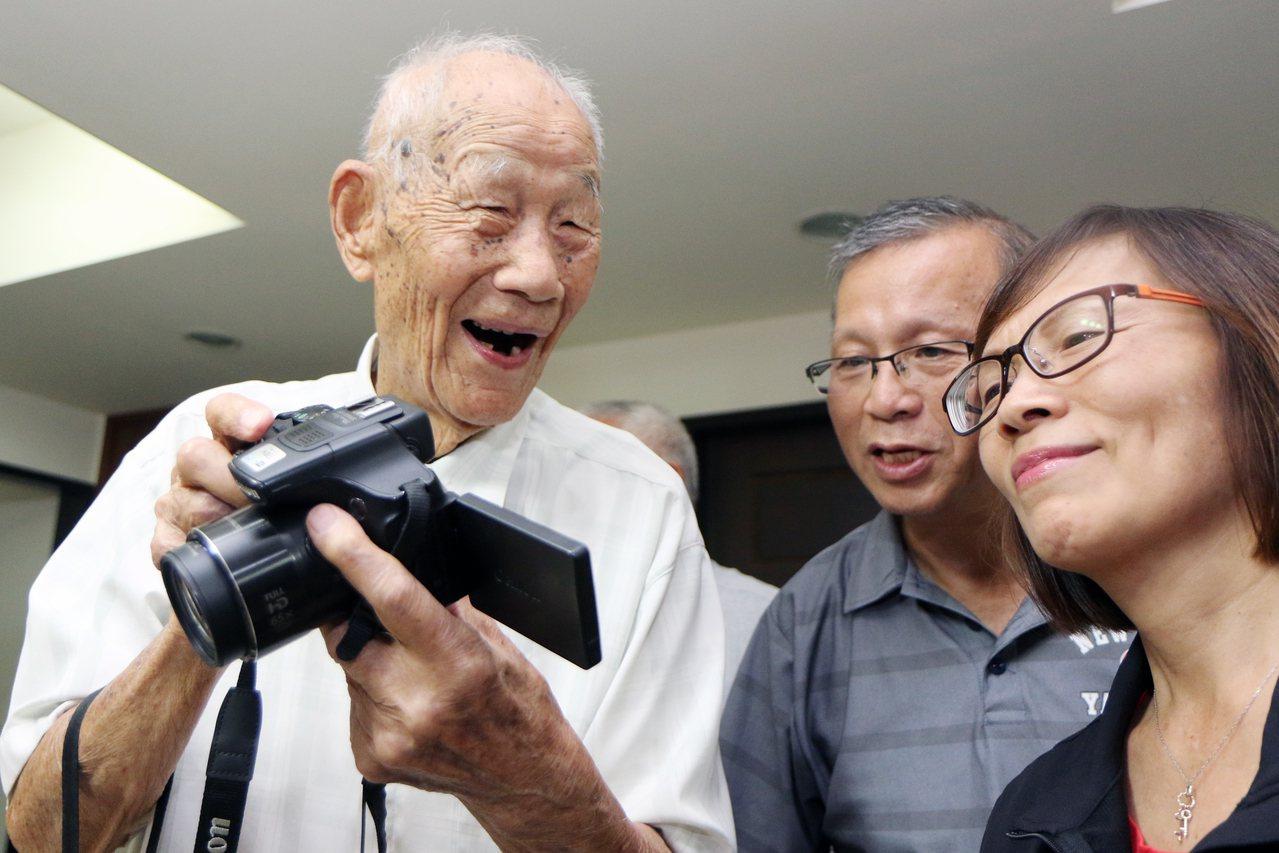 101歲人瑞李昭麟(左)喜好拍照,拿起相機隨手拍照,每張照片對焦準確不失真。記者...