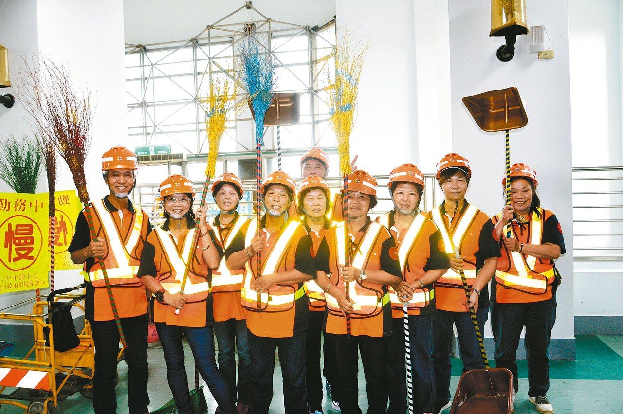 新北市環保局昨天表揚105名績優清潔隊員,汐止區清潔隊帶著平日掃街工具參加。 記...