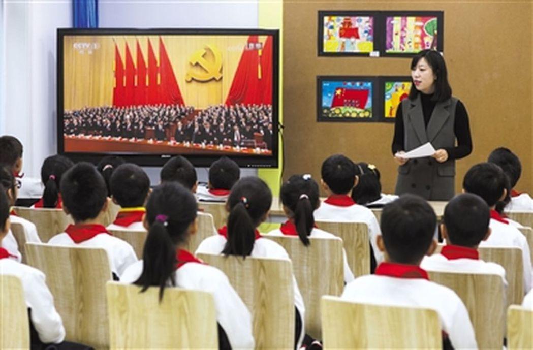 雙榆樹一小全體師生組織收看19大開幕的電視直播。在三年級二班,班主任給孩子們講解...