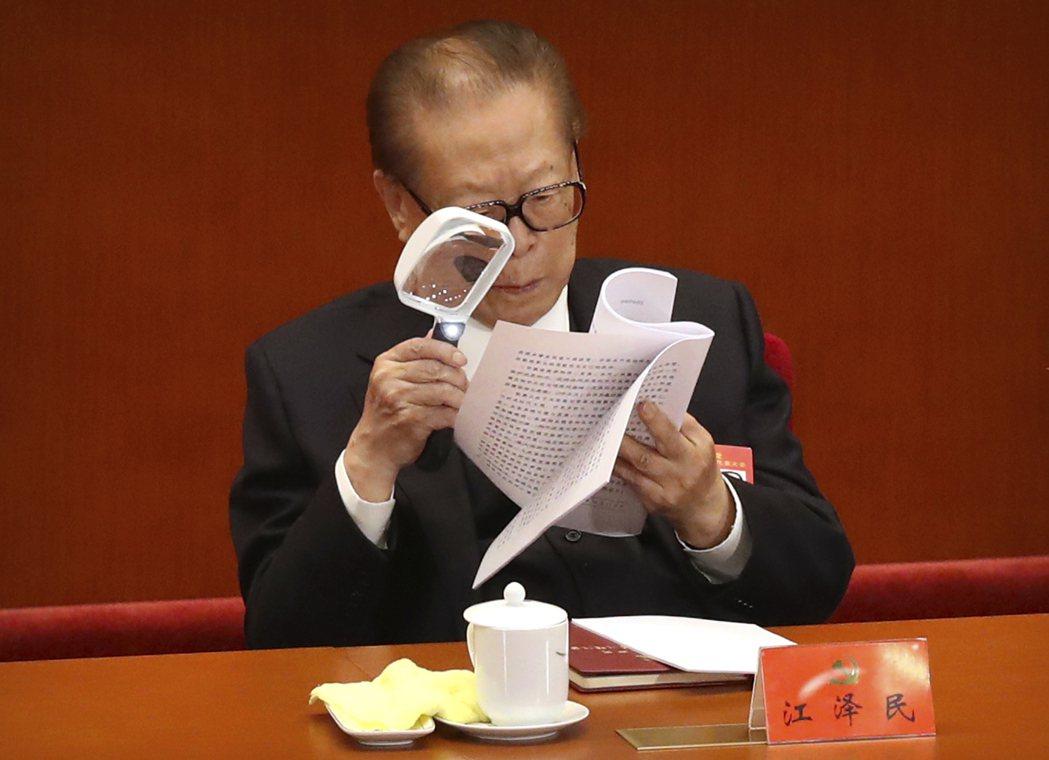江澤民用放大鏡閱讀文件。 美聯社