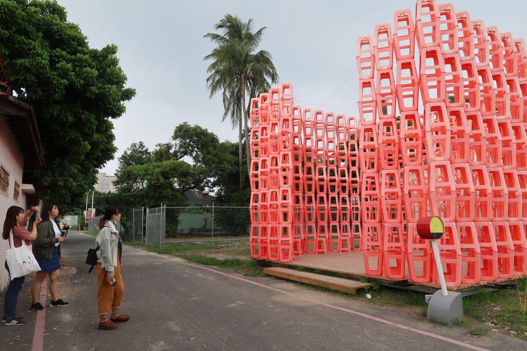 屏東地景藝術節作品之一「圍廬」,是以紅色塑膠椅搭起的凳塔,表現圍爐的概念。記者翁...