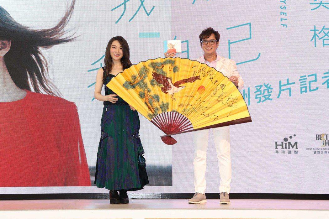 譚詠麟(右)在臨發片記者會送閻奕格巨型紙扇,象徵發片順風順水。圖/華研國際
