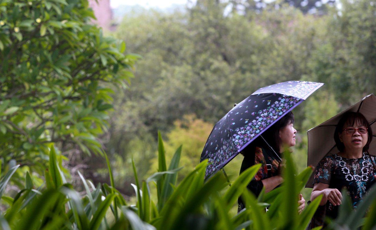 受到東北風影響,迎風面的北部及東北部的天氣皆呈現陰雨,路人撐著傘,令人感到秋天的...