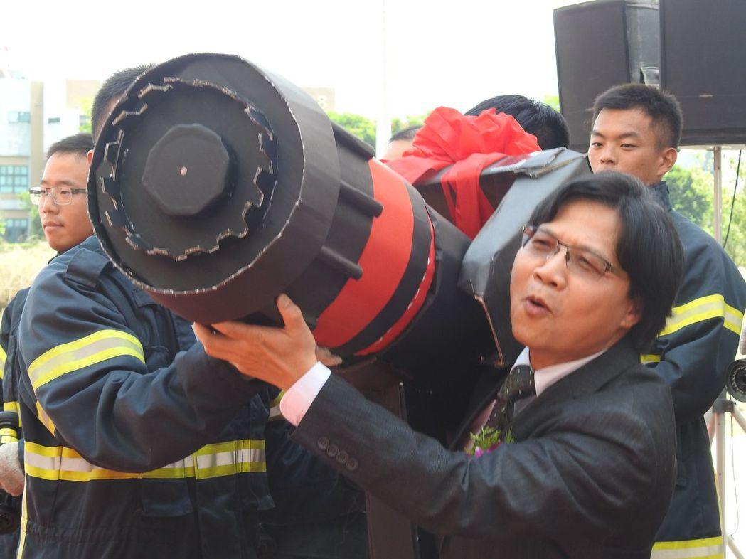 圖為內政部長葉俊榮頒發象徵榮譽和責任的「超大型渦輪瞄子」給消防學員時,搞怪裝出負...