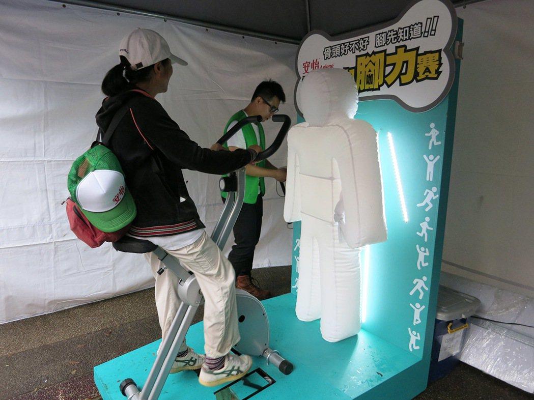 在「A咖大挑戰」活動現場,民眾努力腳踩踏板,直到把充氣娃娃充飽、亮燈才算過關。...