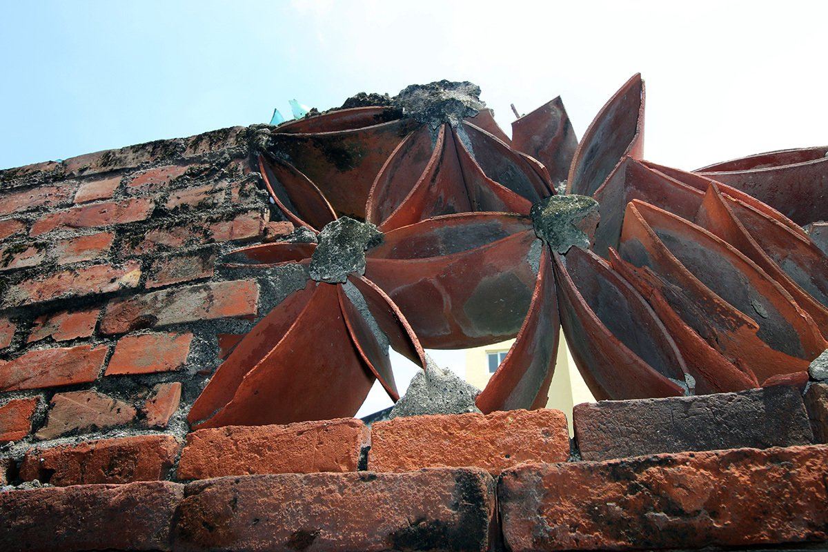 菊花牆的瓦片極薄,如有盜匪攀爬容易踩破而發出聲響。
