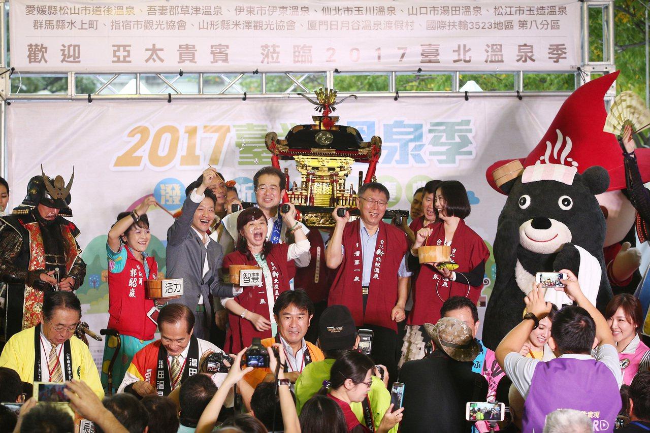 台北市長柯文哲下午出席主題為「潑湯祈福文化慶典」的2017臺北溫泉季開幕式,抬著...